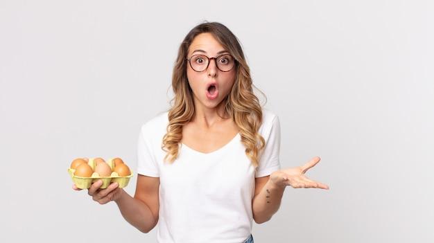 Ładna szczupła kobieta czuje się bardzo zszokowana i zaskoczona i trzyma pudełko z jajkami