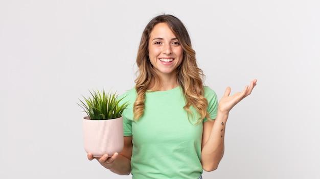 Ładna szczupła kobieta czuje się szczęśliwa, zaskoczona, gdy realizuje rozwiązanie lub pomysł i trzyma ozdobną roślinę