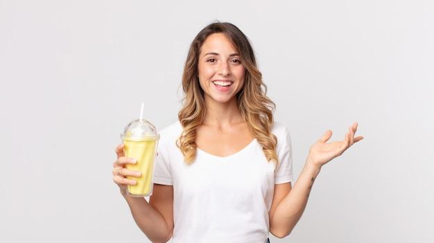 Ładna szczupła kobieta czuje się szczęśliwa, zaskoczona, gdy zdaje sobie sprawę z rozwiązania lub pomysłu i trzyma waniliowy koktajl mleczny