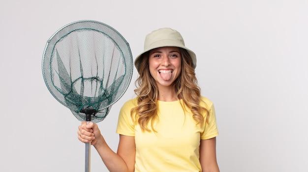 Ładna szczupła kobieta czuje się zdegustowana i zirytowana, wysuwa język w kapeluszu i trzyma sieć na ryby