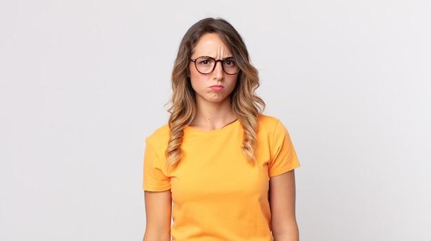 Ładna szczupła kobieta czuje się zdezorientowana i wątpi, zastanawia się lub próbuje wybrać lub podjąć decyzję