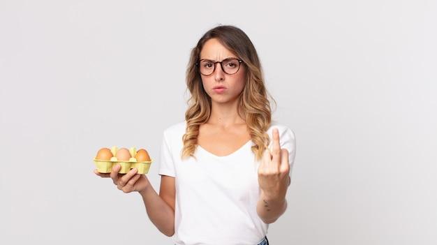 Ładna szczupła kobieta czuje się zła, zirytowana, buntownicza i agresywna i trzyma pudełko po jajkach