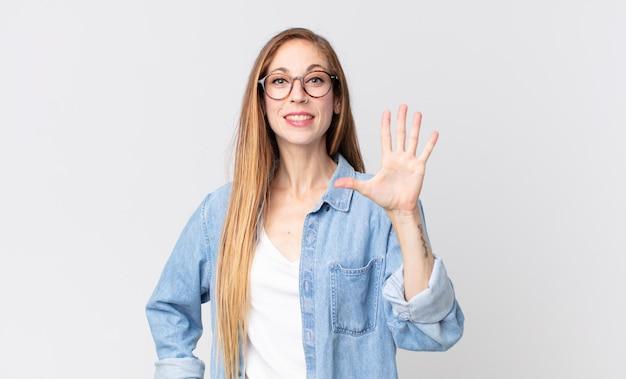 Ładna szczupła kobieta uśmiechająca się i wyglądająca przyjaźnie, pokazująca cyfrę piątą lub piątą z ręką do przodu, odliczającą w dół