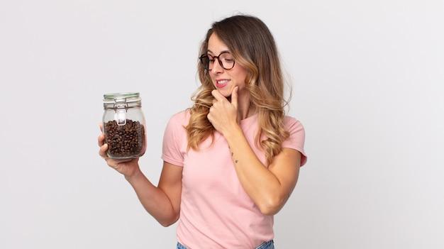 Ładna szczupła kobieta uśmiechająca się ze szczęśliwym, pewnym siebie wyrazem twarzy z ręką na brodzie i trzymająca butelkę ziaren kawy
