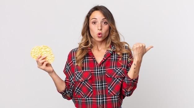 Ładna szczupła kobieta wyglądająca na zdziwioną z niedowierzaniem i trzymająca dietetyczne ciastka ryżowe