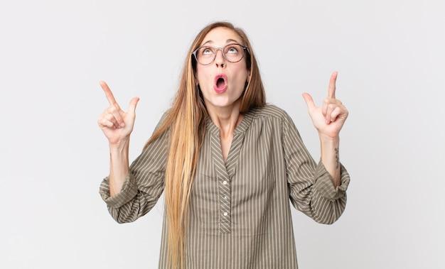 Ładna szczupła kobieta wyglądająca na zszokowaną, zdumioną i z otwartymi ustami, wskazującą w górę obiema rękami, aby skopiować przestrzeń