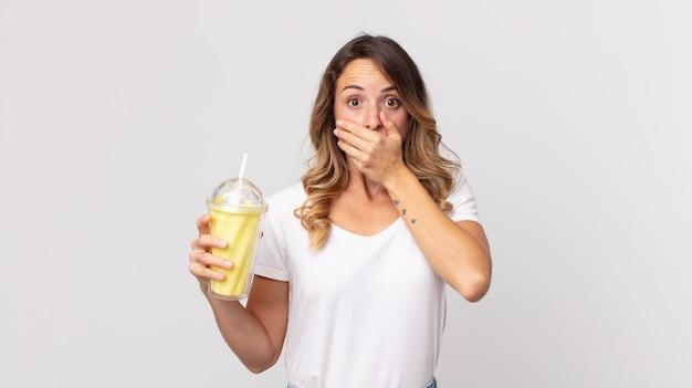 Ładna szczupła kobieta zakrywająca usta dłońmi zszokowana i trzymająca waniliowy koktajl mleczny