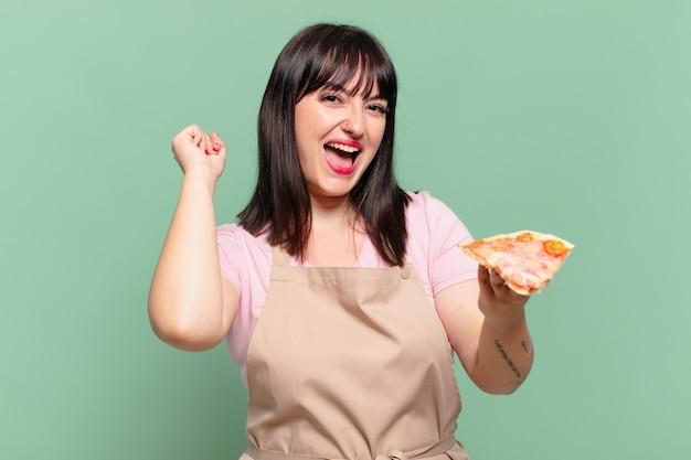 Ładna szefowa kuchni świętująca zwycięstwo i trzymająca pizzę?