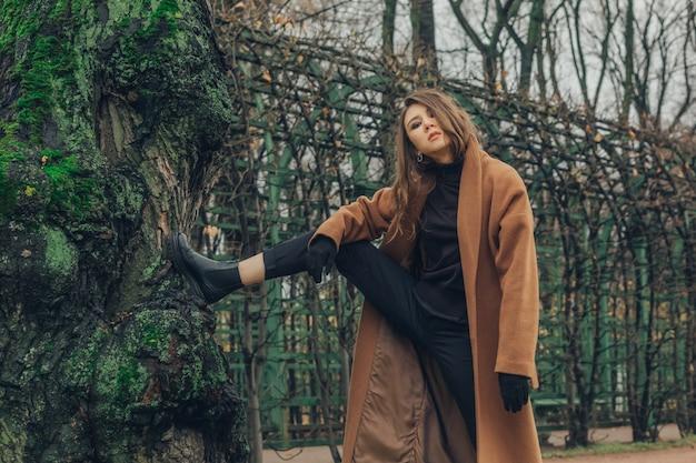 Ładna tatarska fashionistka pozująca przy ogromnym pniu z mchem w parku.