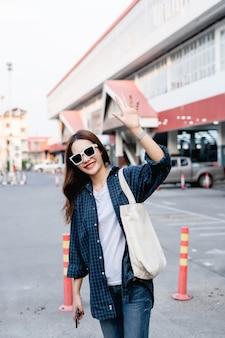 Ładna turystyczna dziewczyna w okularach przeciwsłonecznych, nosząca dużą torbę na ramieniu, stojąca i podnosząca rękę do góry, by powitać i uśmiechnąć się