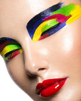 Ładna twarz pięknej kobiety z wielobarwny żywy makijaż oczu na białym tle.