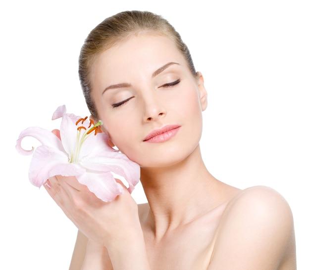 Ładna twarz pięknej młodej kobiety z lilią - na białym tle