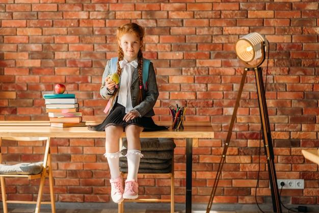 Ładna uczennica siedzi na stole, widok z przodu.