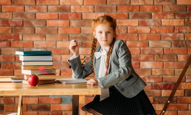 Ładna uczennica siedzi przy stole, widok z boku.