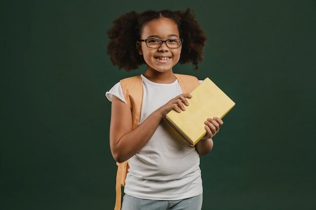 Ładna uczennica trzyma widok z przodu książki