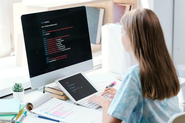 Ładna uczennica z długimi brązowymi włosami siedzi przed monitorem komputera i przygotowuje się do seminarium przed lekcją