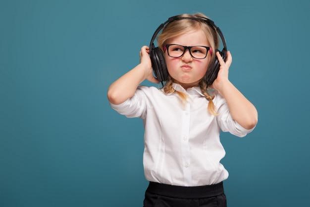 Ładna, urocza dziewczynka w białej koszuli, okularach, czarnych spodniach i słuchawkach