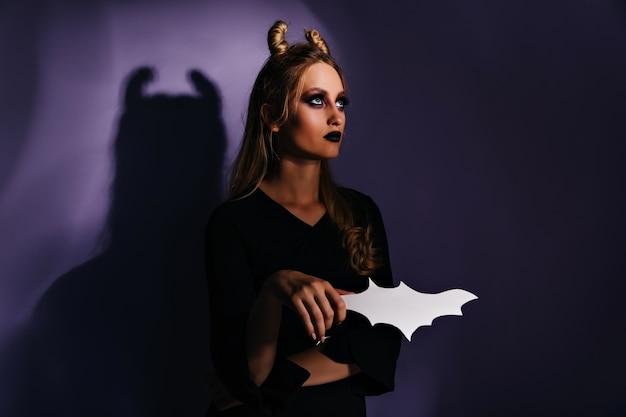 Ładna wiedźma stojąca na ciemnej ścianie i spoglądająca w górę. niesamowita blondynka przygotowuje się do halloweenowej imprezy.