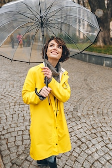 Ładna, zadowolona dorosła dziewczyna w żółtym płaszczu przeciwdeszczowym stojąca pod dużym przezroczystym parasolem z szerokim szczerym uśmiechem w miejskim ogrodzie