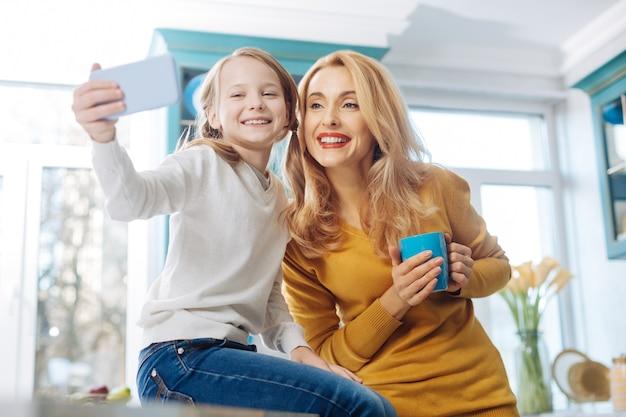 Ładna, zadowolona, jasnowłosa, szczupła matka, uśmiechnięta i trzymająca filiżankę herbaty, podczas gdy jej córka robi zdjęcia