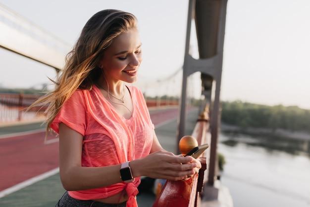 Ładna, zgrabna dziewczyna w wiadomości tekstowej zegarka na rękę. śmiejąc się kaukaski kobieta przy użyciu telefonu po treningu.