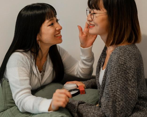 Ładne azjatki próbują produktów do makijażu