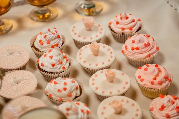 Ładne babeczki z cukrem różanym i białym glazurą stoją na białym