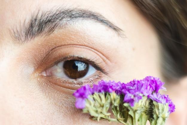 Ładne brązowe oczy kobiety i gęste, idealne brwi z uroczymi suszonymi kwiatami pod oczami