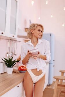 Ładne ciało. młoda blondwłosa kobieta z ładnym ciałem w majtkach i koszuli jedząca płatki zbożowe