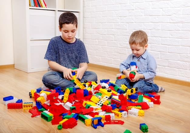 Ładne dzieci bawiące się konstruktorem na podłodze w domu. dzieci w wieku przedszkolnym zabawy. żłobek, rozwój dzieci. na podłodze kolorowe plastikowe klocki.