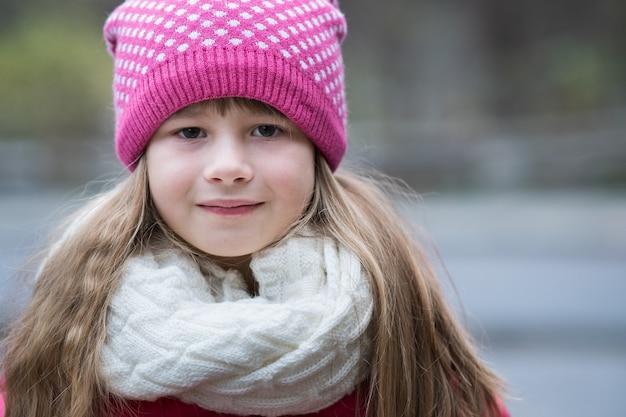 Ładne dziecko dziewczyna w ciepłe zimowe ubrania z dzianiny na zewnątrz.