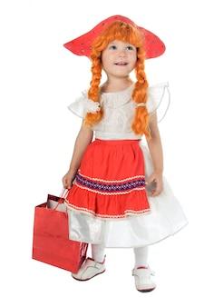 Ładne dziecko w festiwalowej sukience w czerwonym kapeluszu i czerwonym warkoczu na białym tle