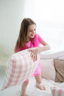 Ładne dziewczynki w różowej sukience księżniczki walczą z cushin