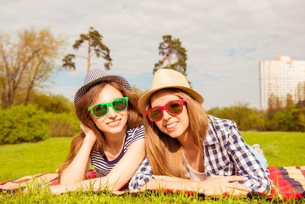 Ładne dziewczyny w kapeluszach i okularach na pikniku w parku