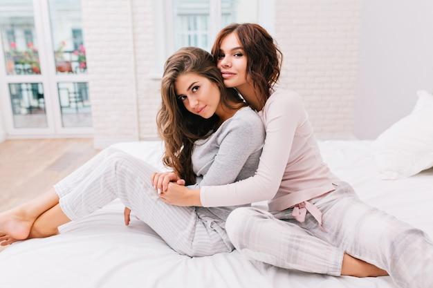 Ładne dziewczyny w piżamie na łóżku. dziewczyna z kręconymi włosami przytula od tyłu inną dziewczynę, patrzą.