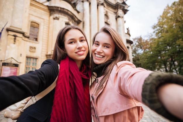 Ładne dziewczyny w płaszczach robią selfie.