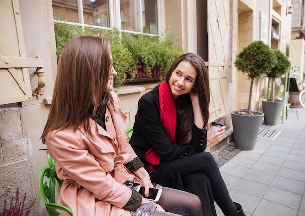 Ładne dziewczyny w płaszczach siedzą na ulicy