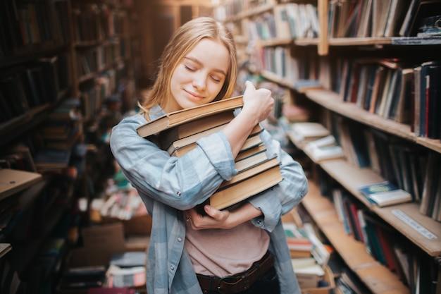 Ładne i ciepłe zdjęcie atrakcyjnej dziewczyny przytulającej książki, które trzyma w dłoniach. zamknęła oczy i położyła głowę na książkach. młoda kobieta wygląda na szczęśliwą.