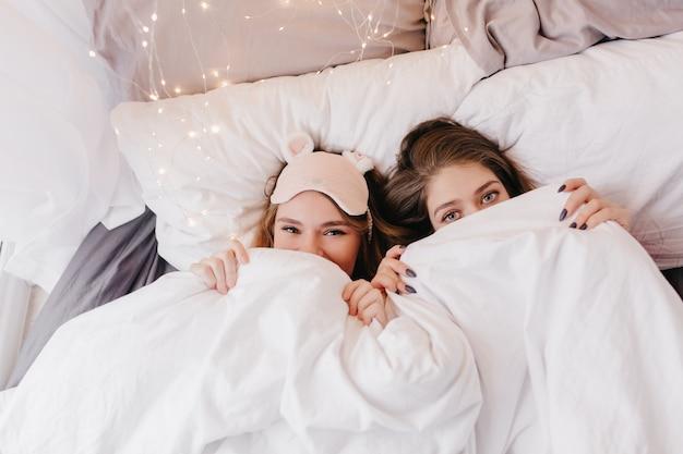 Ładne kaukaskie dziewczyny chowające się pod białym kocem. kryty portret niesamowitych młodych sióstr pozujących rano.