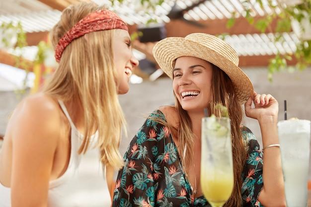 Ładne kobiety odtwarzają się razem w kawiarni, piją świeże koktajle. zrelaksowane urocze suczki wypoczywają podczas letnich wakacji.
