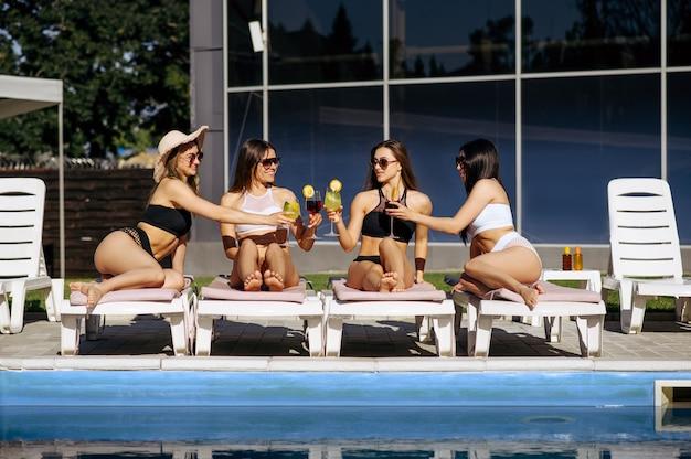 Ładne kobiety w strojach kąpielowych opalające się z koktajlami na leżakach przy basenie w ośrodku. piękne dziewczyny relaksują się przy basenie w słoneczny dzień, letnie wakacje atrakcyjnych dziewczyn