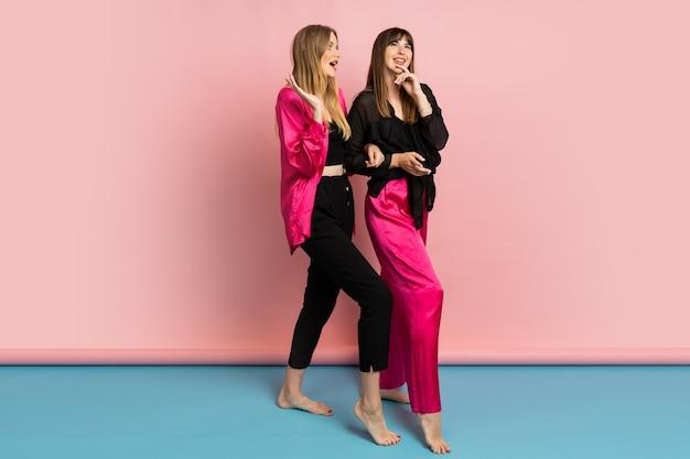 Ładne kobiety w stylowych, kolorowych strojach, bawiące się na różowej ścianie