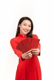 Ładne kobiety z ao dai, w księżycowy nowy rok czerwona paczka jest prezentem pieniężnym