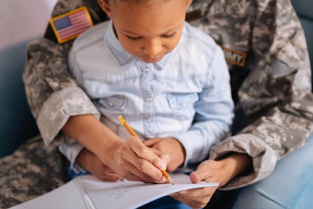 Ładne litery. żywa, inteligentna dziewczyna pracująca nad swoim pismem przy pomocy swoich matek podczas wspólnego weekendu