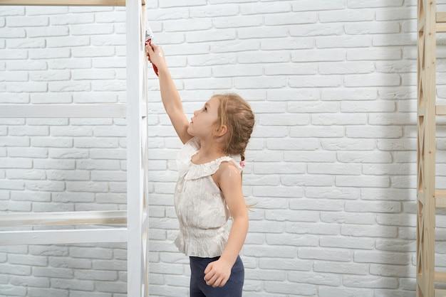 Ładne malowanie dziecka za pomocą pędzla i białego drewnianego stojaka