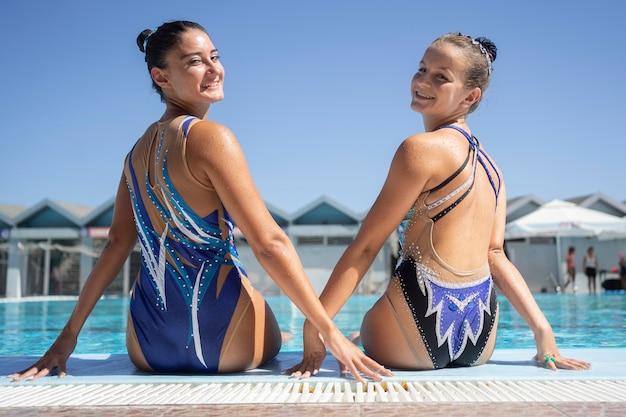 Ładne młode dziewczyny pozują przy basenie