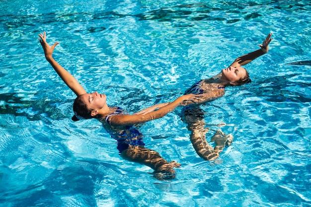 Ładne młode dziewczyny spędzają czas na basenie