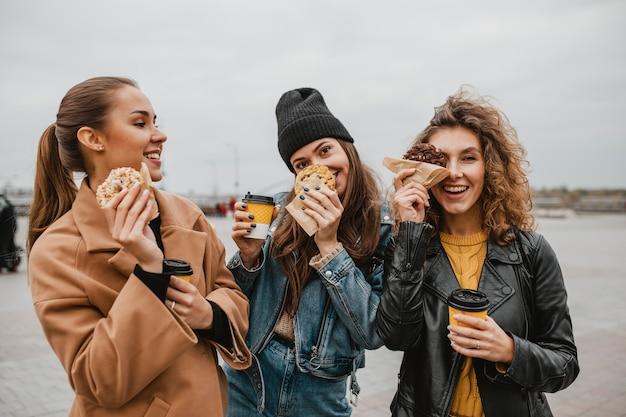 Ładne młode dziewczyny wspólnie spożywające słodycze