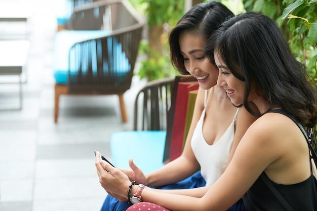 Ładne młode kobiety mają krótką przerwę po wspólnych zakupach w centrum handlowym i omawianiu zdjęć znajomych ...