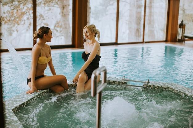 Ładne młode kobiety siedzą i relaksują się przy wannie z hydromasażem